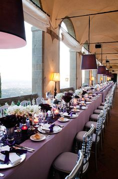 Three long dinner tables are dressed in purple linens and topped with silver charger plates.
