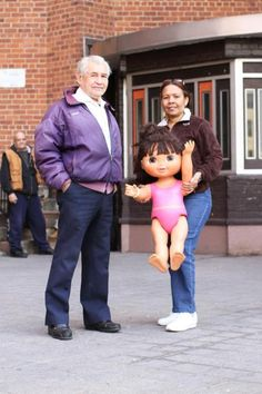 """Saw a woman across the street holding a giant Dora the Explorer doll.    When I asked her where she got it, she told me the man in the purple jacket had given it to her— as a gift for her granddaughter.    When I asked the man where the doll came from, he said:  """"The trash, but all she needs is a quick trip to the salon."""""""