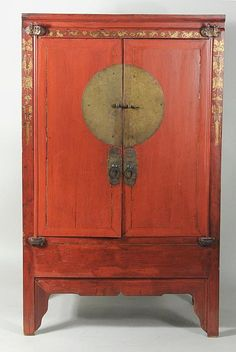 "Chinese red lacquered two door cabinet, 19th century, doors with large brass medallion, lock, and pulls. 68"" high, 41 1/2"" wide, 24"" deep."