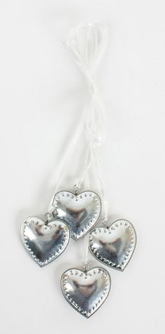 Cluster of Tin Hanging Hearts Cluster of 4 small tin hanging hearts hung with a white ribbon.  The perfect decorative item for a wedding or simply around the house.  Size -  4 x 4 x 24cm