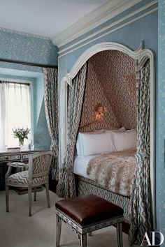 In an attic room for guests, the bed is contained in a chintz-lined niche with a Rococo frame. http://amzn.to/2rWsgFP