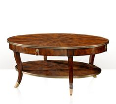 A mahogany oval cocktail table, with a brass bound top and undertier, the top fitted with four leather inset slides, on sabre legs. The original Regency.