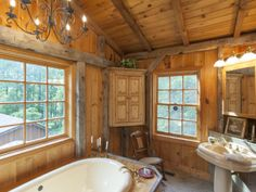 FARMHOUSE – INTERIOR – vintage early american farmhouse showcases raised panel walls, barn wood floor, exposed beamed ceiling, and a simple style for moulding and trim, like in this farmhouse bathroom in titusville, new jersey.