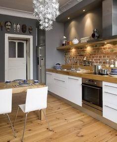 nowoczesna biała kuchnia z detalami ze stali,szarymi i ceglanymi ścianami i drewnianą podłogą