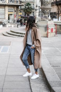Overside camel coat, grey textured sweater, distressed 7/8 denim, white sneakers.