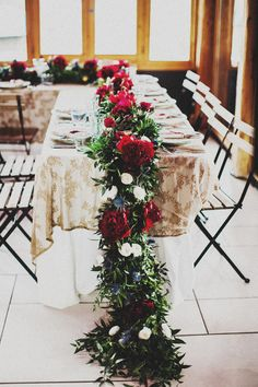 Head Table. Lavishly floral garland with burgundy peonies, gentle white ranunculuses, blue thistle, deep green foliage.