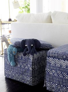 Blue and white patterned storage stools make for chic additional seating and an easy place to stash toys and extra pillows.