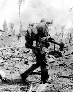 A US Marine carrying a wounded Japanese POW on his shoulders towards the rear lines somewhere in the Pacific, c. 1943