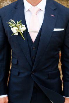 noivo de fato azul marinho com gravata e camisa claras