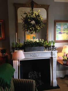 Mantel piece decoration: old metal box stuffed full of white Hellebores. Christmas roses and white hyacinths in metal goblets, flanked with silver candle sticks for extra sparkle and height.