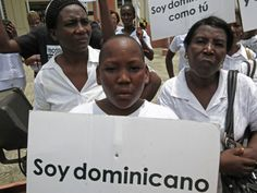 "A youth of Haitian descent holds a sign that reads in Spanish ""I'm Dominican."""