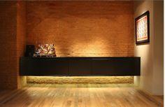 Aparador preto flutua sobre parede de tijolos aparentes e chão de madeira na sala