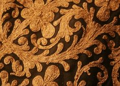 A detail of gold thread couched in leaf and flower motifs onto a black Albanian giubba fron the Costume Gallery at Bankfield Museum © Calderdale MBC