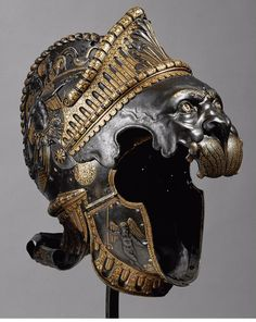 A nemean lion from an all'antica ensemble with a round sign (A 693a)  Helmet Milan Around 1541 OWNER Emperor Charles V son of Philip of Hapsburg (1500 - 1558) - GND MANUFACTURER Filippo Negroli, (Plattner) ( born 1532 - 1553, active in Milan) - GND MATERIAL / TECHNOLOGY Dark browned, driven, gold-exchanged iron (CA)  PICTURE RIGHT Kunsthistorisches Museum Wien, Hofjagd- and Rüstkammer
