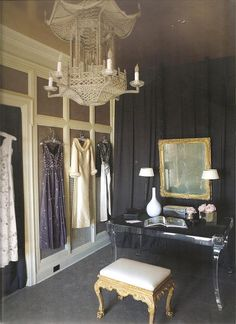 Glamour dressing room w/ black draped wall, pagoda chandelier, and lucite vanity; Mary McDonald