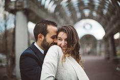 The bride and groom holding one another under an archway and smiling near Faneuil Hall in Boston, Massachusetts | Wedding Photography