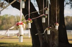 hanging flowers in milk glass containers for ceremony decor - via Every Last Detail