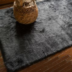 The stunning visual impact of this attractive, machine-made rectangular black faux-sheepskin rug is easily matched by the luxurious softness of its thick acrylic shag. This beautiful rug will be a unique and comfortable focal point in any room.