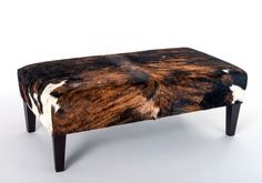 Beautiful tri-colour brown, black and white cowhide coffee table ottoman with wood legs by Gorgeous Creatures. Use an ottoman like this instead of a coffee table.