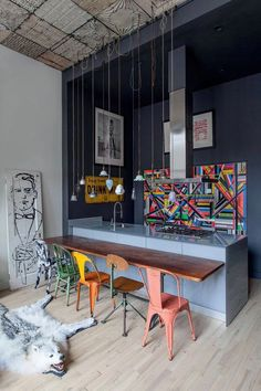 The tin ceiling of this Chelsea loft is paired with wonderful art from the likes of Alex Katz, James Rosenquist and Damien Hirst. Animal rugs and mismatched chairs pull together this eclectic room.