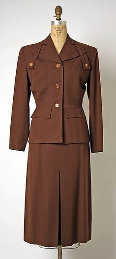 Suit by Gilbert Adrian, 1948, brown wool and rayon blend. Bands and buttons fix the extended collar lapel in place.