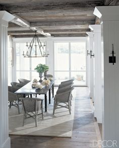 Beautiful dining room with rustic wood beam ceiling, wood floors, area rug, dark wood table and white walls