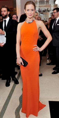 Emily Blunt at the 2012 Women of the Year Awards wearing an Alexander McQueen orange halter gown and satin clutch.