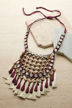 Artisan-crafted, our Trina Statement Necklace makes a very memorable statement! Sparkling rhinestones outline a bib of woven metallic paillettes and glass cabochons. It's all finished off with a dramatic fringe of silky tassels.