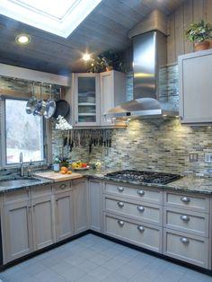 Renovated kitchen features white oak rift cut 1/4 sawn wood with greige stain. Backsplash of irredescent green glass tiles ties it all together ....