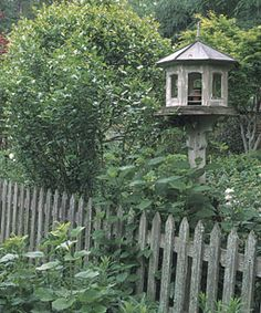 A traditional picket fence, with its recurrent vertical lines, visually defines a cottage garden.