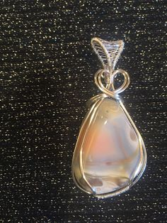 Handmade wire wrap pendant with a lovely Botswana Agate! Wrapped in silver plated wire with a little heart design up top. This Botswana Agate has such a sweet energy and is one of the prettiest I have seen; the pattern of it kind of reminds me of a sunset over a tidepool! The pendant