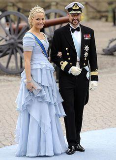 Principe Haakon y La princesa Mette-Marit de Noruega que llevó un vestido de seda color celeste, con cuerpo tableado y falda de volantes asimétricos. Como complemento, eligió una cartera de mano en tono gris piedra.