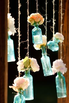 Ashlee Raubach Photography  Easy DIY wedding decorations... we built a wooden frame, attached 7 hooks to the top, and hung mismatched blue vases from twine. We used this as a back drop for the cake table.