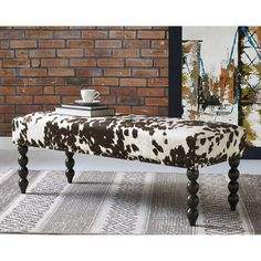 Spruce up your home with this Para Bench. Upholstered with faux cowhide, this wooden piece works as a bench or ottoman. The intricate Louis XIII legs are hand-carved from birch for sturdy support.