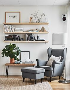 Three wall shelves and a bench are placed near a great armchair and footstool.