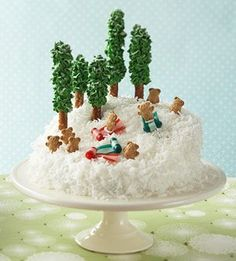 Sledding Party Cake-  Create your own winter wonderland on top of this coconut-covered cake. Frosting-topped pretzels make a miniature pine forest, while bear-shaped cookies on fruit-leather sleds ma