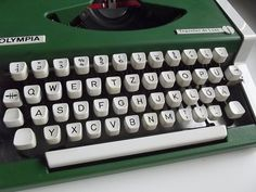 Beautiful green manual portable typewriter Olympia Traveller de Luxe with green plastic box. Germany 1970s.