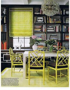 lime green faux bamboo chairs, glossy white table, lime green rug, lime green roman shade, crystal chandelier and built-ins bookshelves library.
