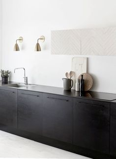 beautiful black minimal kitchen with gold lamps