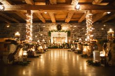 Candlelit ceremony with rustic tree stumps, pine boughs, raw cotton and white roses, and an old fireplace mantel.  Lauren Fair Photography  venue: General Potter's Farm in State College, PA