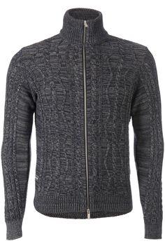 Prachtig gebreid grijs gemeleerd vest uit de jeans lijn van Armani. Over het voorpand en de mouwen lopen verschillende soorten kabels. De kraag en het rugpand heeft weer een ander patroon. Rechts onderin zit een Armani JEans logo. Het vest is hoofdzakelijk gebreid van katoen.