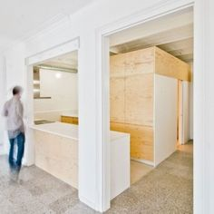 Spanish architect Carles Enrich has inserted a plywood box beneath the vaulted ceilings of an early 20th-century apartment in Barcelona to create a new bathroom and kitchen unit.