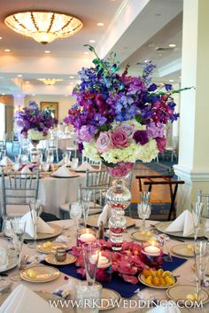 Full lush floral centerpiece of purple, white and blue flowers: purple stock, purple mokara orchids, blue dendrobium orchids, blue delphinium, purple and lavender carnations and lavender roses