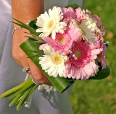 This bouqet is so cute..  Daisies are great if you want a simple bridal bouquet. Daisies are a symbol of freshness, modesty and simple beauty. The pink daisy is a popular choice, you can find them in s variety of colors from fuchsia to dark pink.