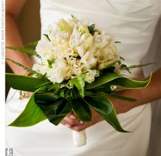 Bouquet of gardenias mixed with ginger surrounded by a collar of ti leaves