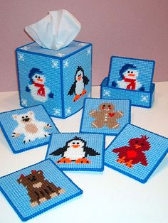 """Darling Winter Buddies include a Snowman, Penguin, Polar Bear, Reindeer, Cardinal and Gingerbread Boy. Size: Tissue Box Cover: Fits boutique-style tissue box. Coaster: About 4"""" x 4"""". Coaster Holder: 5 1/2""""W x 1 1/2""""H x 2""""D. Made with medium (worsted) weight yarn and 7-count plastic canvas. Skill Level: Easy"""