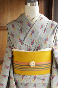 繊細な横ストライプが織り出された曇り空のようなグレーの地に、青、赤、黄色、緑のクレパスで描いたような絣模様が織り出されたウールの単着物です。