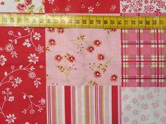 Katoenen stof met een print van grote en kleine bloemen in quiltvakken, hoofdkleuren: roze, felgroen en wit