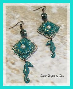 """Adventures In The Sea"" Seahorse Chandelier Earrings .. A sweet flower with a flat back pearl in the center is attached to a filigree stamping and dangles beneath a metal rhinestone bead .. Seahorses dangle at the bottom of the the earrings .. .. For Sale $27.00 .. https://www.etsy.com/shop/CleverDesignsbyJann"