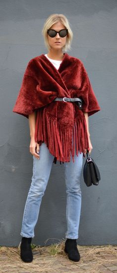 A fringe poncho, jeans, and a leather belt
